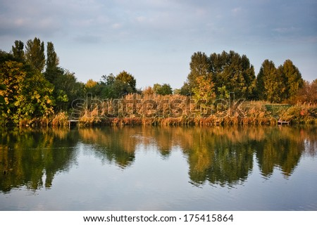 Beautiful calm autumn waterfront landscape trees reflecting on the smooth water surface on the warm afternoon sunset - stock photo