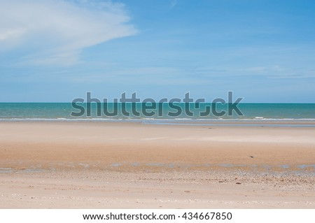 Beautiful calm beach and cloudless blue sky with ocean at low tide, with copy space. - stock photo