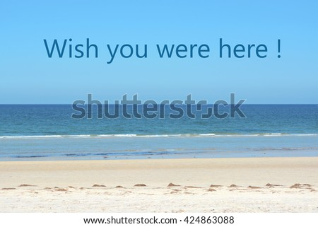 Beautiful calm beach and cloudless blue sky with ocean at low tide, with Wish You Were Here vacation greeting sample text.   - stock photo