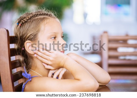 Beautiful calm little girl sitting at wooden table - stock photo