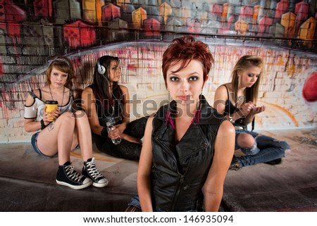 Beautiful calm red hair young woman with distracted friends - stock photo