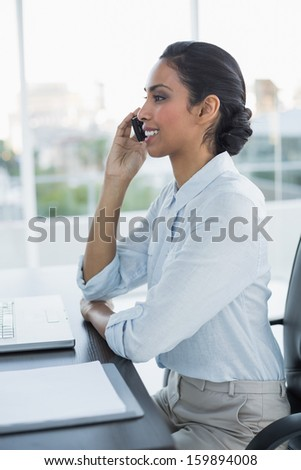 Beautiful calm woman phoning with her smartphone sitting at her desk in the office