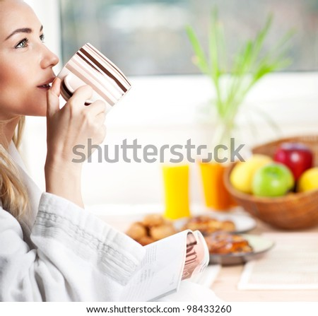 Beautiful calm young woman having morning coffee, relaxing hot drink, happy female holding cup of tea, pretty blond girl eating and drinking healthy food at home, health care and dieting concept - stock photo