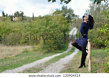 Beautiful calm young woman is posing in the country early autumn time, Tuscan, Italy - stock photo