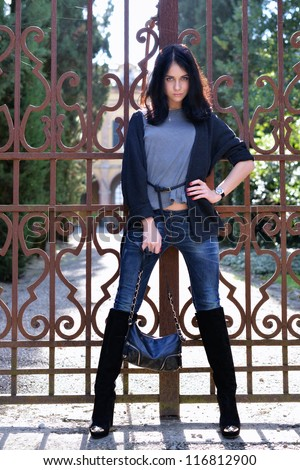 Beautiful calm young woman standing at the iron medieval gate of fence of the old castle, Tuscan, Italy - stock photo