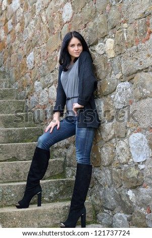 Beautiful calm young woman standing on the stairs of the old castle, Tuscan, Italy - stock photo