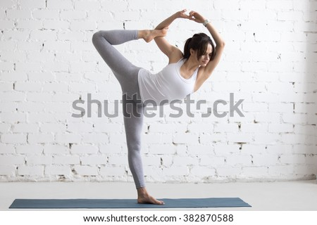 Beautiful calm young woman working out indoors, doing yoga exercise on blue mat, variation of Natarajasana, Lord of the Dance, King Dancer or Standing Mermaid Pose, full length - stock photo