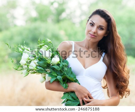 Beautiful candid carefree adorable woman in field with flowers at summer sunset - stock photo