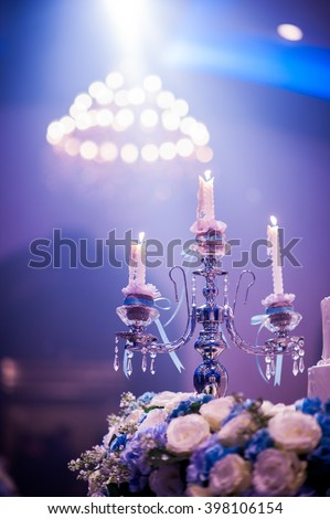 beautiful candle with Big crystal chandelier under nice ceiling in grand ballroom on blue light and blurred background in Party Time - stock photo