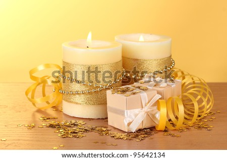 Beautiful candles and gifts on wooden table on yellow background - stock photo