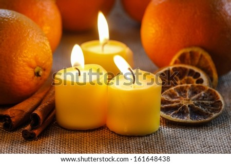 Beautiful candles and juicy oranges on jute table cloth - stock photo