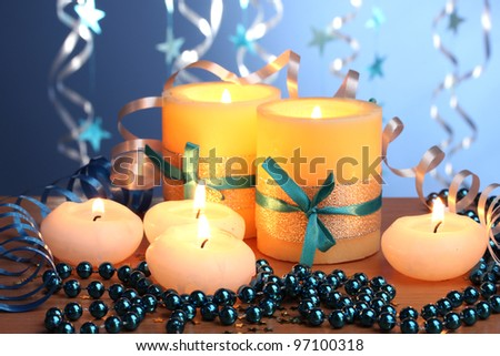Beautiful candles, gifts and decor on wooden table on blue background - stock photo