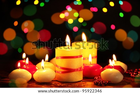 Beautiful candles on wooden table on bright background