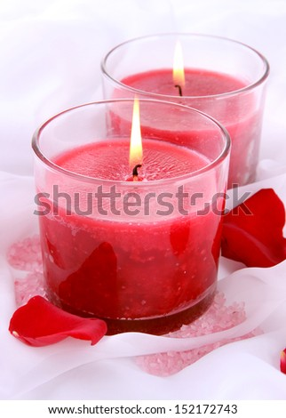 Beautiful candles with flowers on white cloth, close up