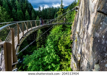 Beautiful Capilano Cliff Walk Suspension Bridge with Tourists Enjoying the View, in Vancouver. - stock photo