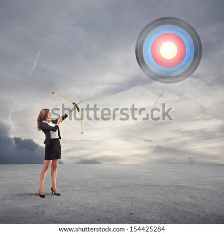 beautiful career woman pulls arrow with bow - stock photo
