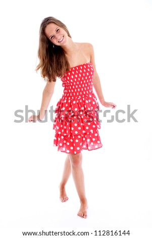 Beautiful carefree barefoot teenager Beautiful carefree barefoot teenager with a vivacious smile walking across the frame in a pretty red and white polka dot sundress - stock photo