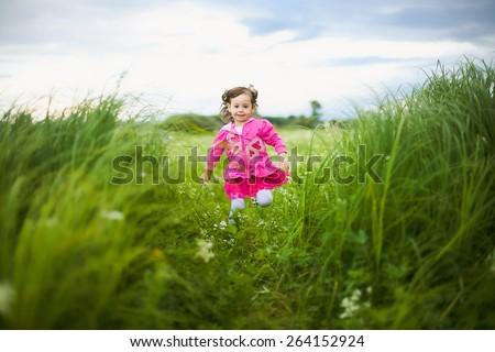 beautiful carefree girl running outdoors in field with high green grass.freedom concept. child playing alone in meadow. happy childhood - stock photo