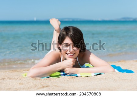 Beautiful carefree young woman lying on her stomach on a towel on the sand sunbathing on the beach smiling happily at the camera against an ocean background - stock photo