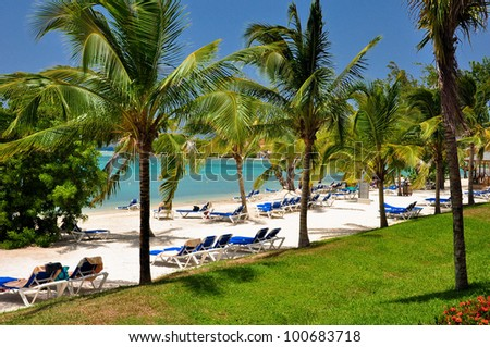 Beautiful caribbean beach with sun beds - stock photo