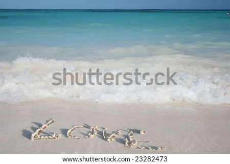 Beautiful Caribbean tropical beach with a big heart drawn on white sand and green ocean, suitable background for a variety of traveling and holiday/love designs