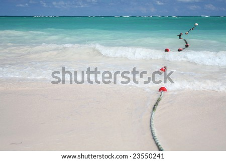 Beautiful Caribbean tropical beach with white sand and bouys floating in green ocean, suitable background for a variety of designs. FOCUS on waves rolling onto beach
