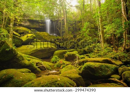 Beautiful cascade falls over mossy rocks in tropical forest, Thailand. - stock photo