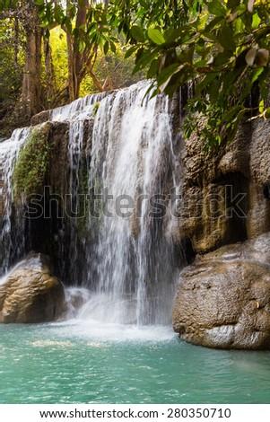 Beautiful cascade waterfall in deep evergreen forest, Erawan National Park in Kanchanaburi, Thailand - stock photo