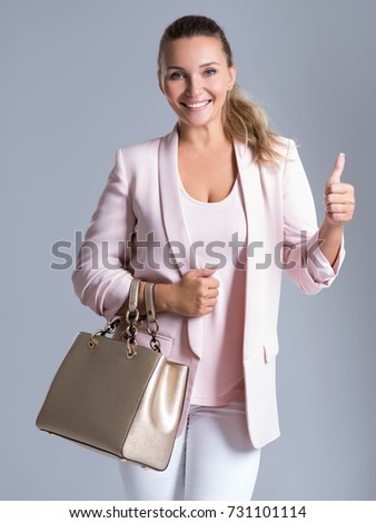 Beautiful casual adult smiling woman with thumb up. Trendy female with handbag