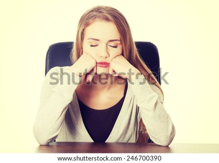 Beautiful casual bored or sleeping student woman by a desk. - stock photo