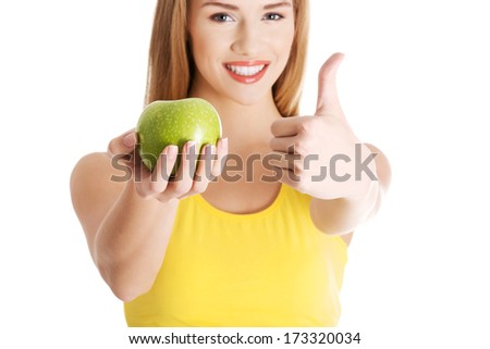 Beautiful casual caucasian woman holding fresh green apple. Isolated on white. - stock photo