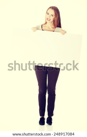 Beautiful casual woman holding copy space and advertising. - stock photo