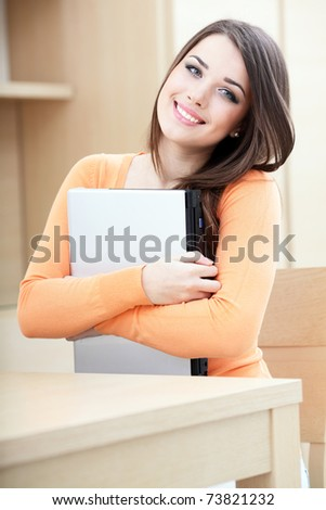 Beautiful casual woman hugging her laptop at home