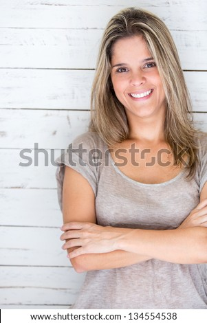 Beautiful casual woman leaning on a wooden wall and smiling - stock photo