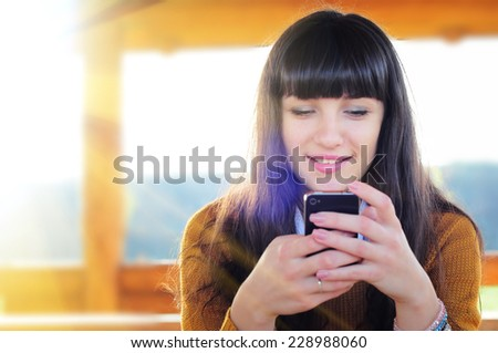 Beautiful casual woman texting on her cell phone - stock photo
