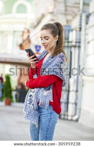 Beautiful casual woman texting on her cell phone on summer street city - stock photo