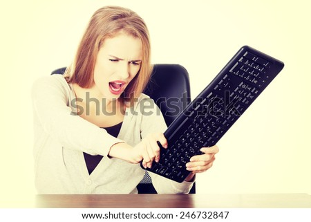 Beautiful casual woman trying to destroy keyboard.