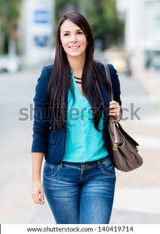 Beautiful casual woman walking outdoors holding her purse