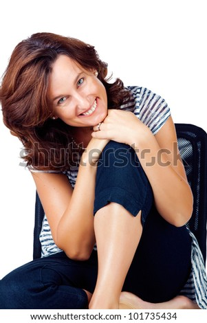 Beautiful casual young woman in her 30s sitting on a chair against white background and wearing top with stripes and jeans - stock photo