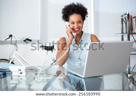 Beautiful casual young woman using telephone and laptop in office - stock photo