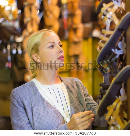 Beautiful casually dressed caucasian blond woman shopping for new leather sandals on crafts market in Chania, Crete, Greece.