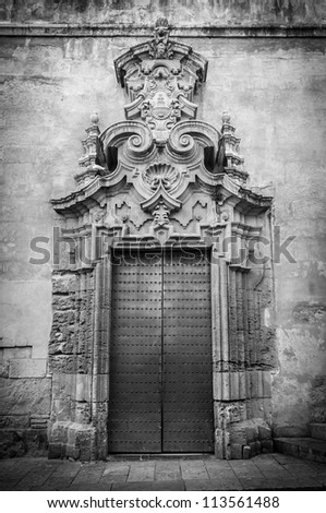 Beautiful cathedral in Toledo, Spain. Famous tourist and religious place in Europe. Main entrance with two dark massive doors. Arch above doorway with ornate details. - stock photo