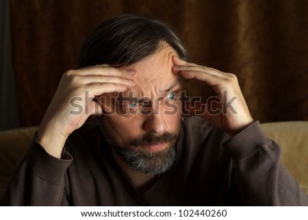 Beautiful Caucasian adult man sitting at a table on a brown background