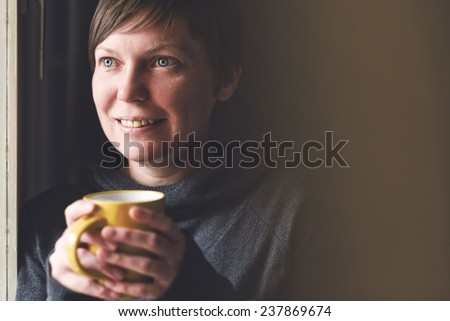 Beautiful caucasian adult smiling woman drinking and enjoying cup of coffee in dark room. Selective focus with shallow depth of field.