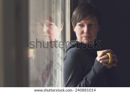 Beautiful caucasian adult woman drinking cup of coffee in dark room by the large window. Selective focus with shallow depth of field. - stock photo