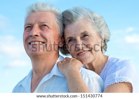 Beautiful Caucasian aged couple outdoors on a sky background - stock photo