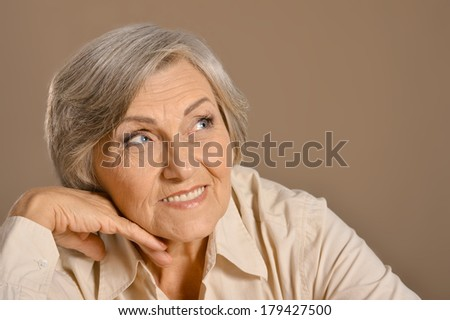 Beautiful Caucasian aged woman sitting on a brown background