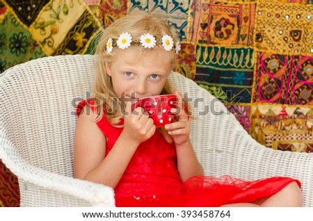 beautiful caucasian blond girl sitting and holding red cup of tea - stock photo