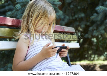 Beautiful Caucasian blond girl sitting on old park bench playing on smart phone - stock photo