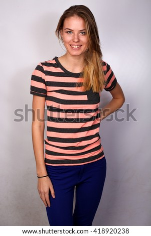 beautiful Caucasian blond girl student posing in studio isolated on white background, striped polo. hand on waist. smile - stock photo